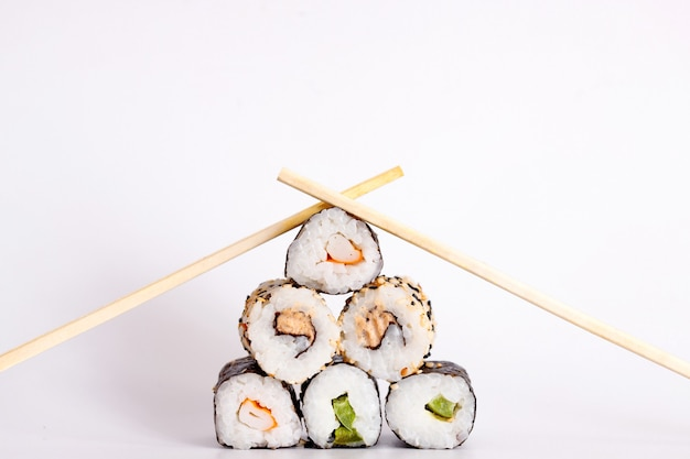 Eating sushi with chopsticks. sushi roll japanese food in restaurant isolated on white background.