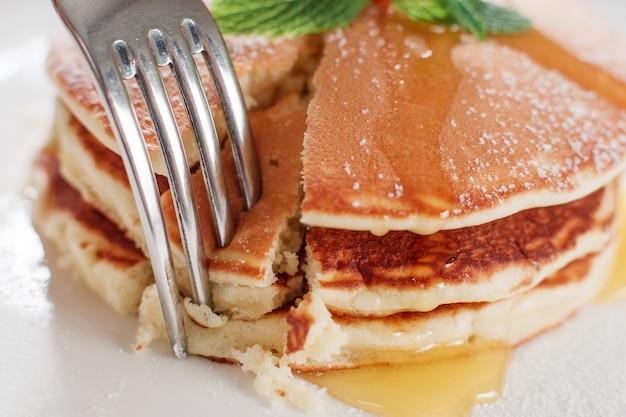 蜂蜜のクローズアップで甘いアメリカのパンケーキを食べる。白いプレートの背景にクレープとフォーク。伝統的なアメリカ料理。