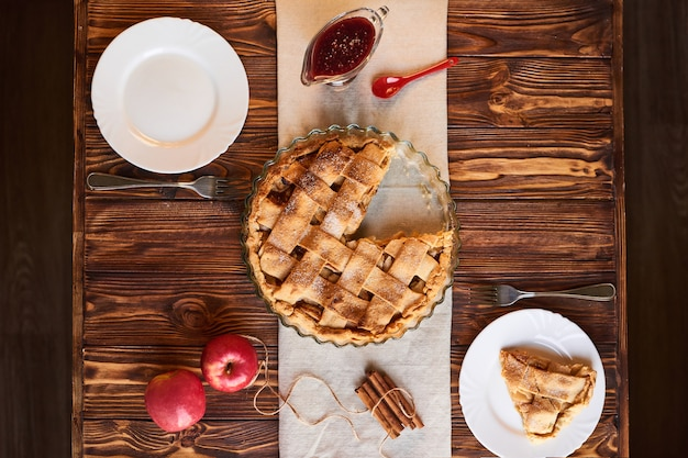 Eating sweet food context. traditional holidays apple pie, slice on white plate and apples. relishing sweet treats