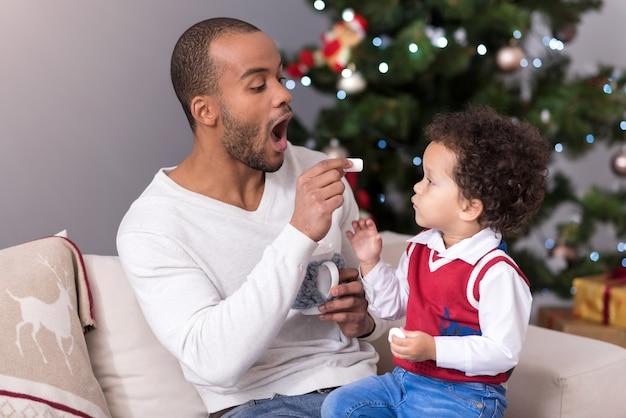 Есть сладости. заботливый, симпатичный и позитивный отец держит зефир и предлагает его своему сыну, проводя с ним время