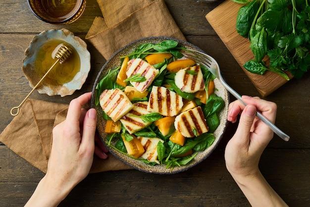 トマトほうれん草ハルーミチーズカシューハニー顔のない女性の手でおいしいサラダを食べる