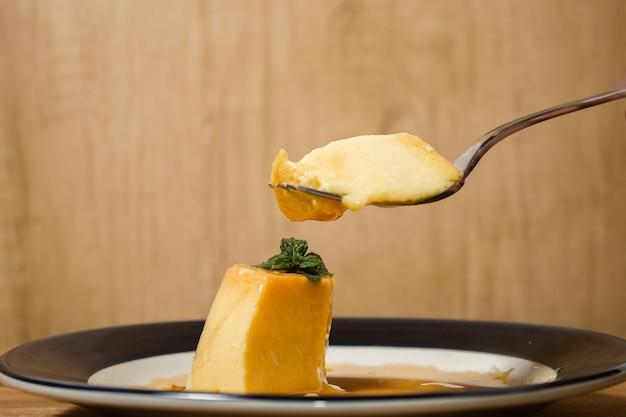 Отведать восхитительный типичный аргентинский и южноамериканский десерт под названием flan с карамелью. наблюдают за рукой посетителя. концепция естественного и здорового питания.