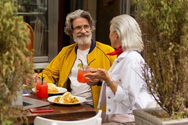함께 식사. 수염을 기른 행복한 남자가 거리 카페에서 아름다운 아내와 이야기하고 점심을 먹고 있습니다.
