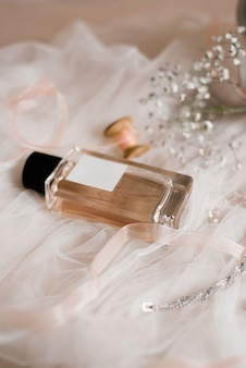 オードトワレとコスチュームジュエリー、白いチュールにカスミソウの小枝。花嫁の朝