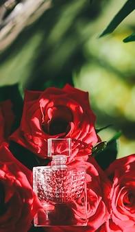 オードトワレまたは香水と赤いバラの香水を豪華なギフトの美しさのフラットレイの背景と宇宙として...