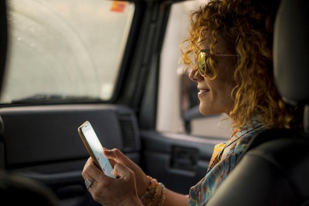 美しい中年女性は、乗客のように車に乗って旅行している間、ソーシャルメディアで自分のプロフィールを携帯電話で確認
