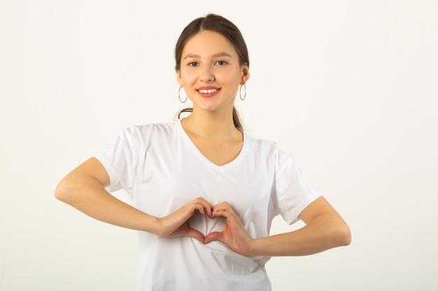 손 제스처와 흰색 배경에 흰색 티셔츠에 eautiful 젊은 여자