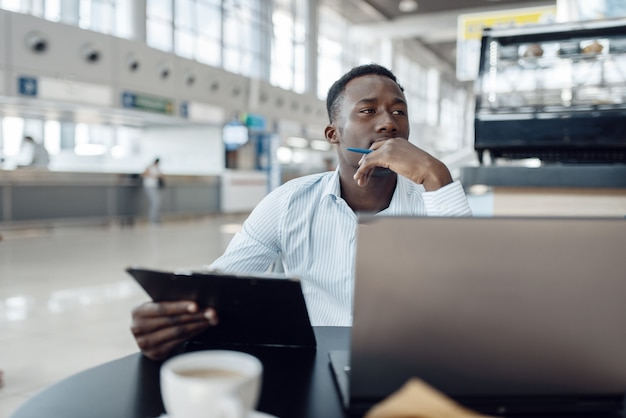 Ebony businessman sitting at laptop in car dealership. successful business person on motor show, black man in formal wear, automobile showroom