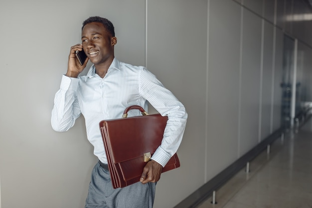 Ebony businessman with briefcase talking by phone in office hallway. successful business person negotiates in corridor, black man in formal wear