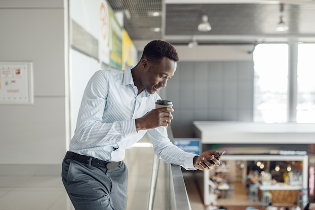 Ebony businessman with cup of coffee, food-court