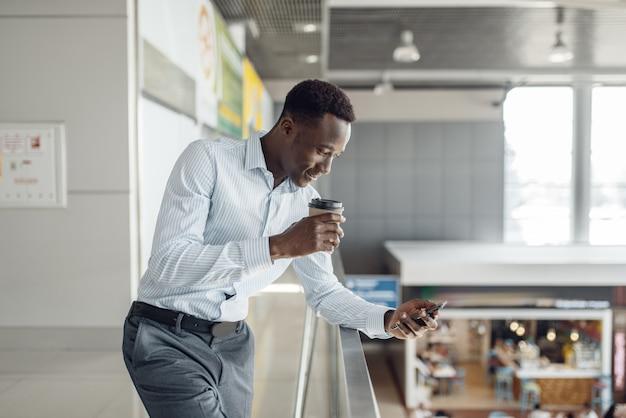 Чернокожий бизнесмен с чашкой кофе, фуд-корт