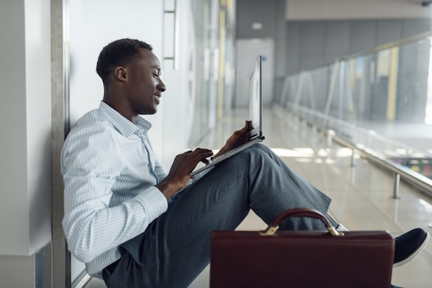 Черный бизнесмен с ноутбуком, сидя на полу