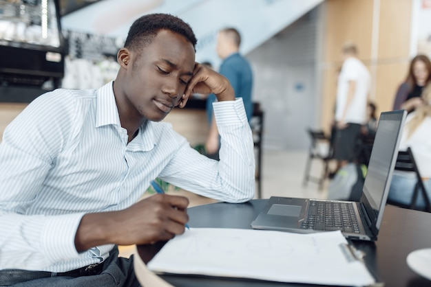 Ebony businessman working on laptop in office. successful business person at his workplace, black man in formal wear
