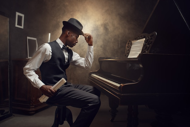 Ebony grand piano player, jazz musician. performer poses at musical instrument before playing melody