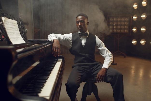 黒檀のグランド ピアノ奏者、スポット ライトを備えたステージ上のジャズ パフォーマー。コンサートの前に楽器でポーズをとるミュージシャン