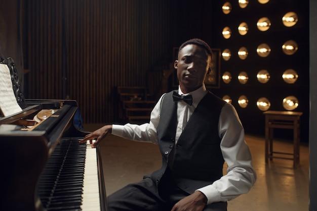 スポット ライトでステージ上の黒檀のグランド ピアノ奏者。コンサートの前に楽器でポーズをとるパフォーマー