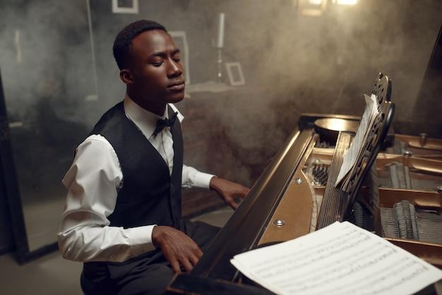 Эбеновый рояль, исполняющий классическую музыку. исполнитель позирует у музыкального инструмента, джазовый музыкант