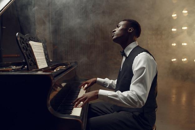 スポット ライトを当ててステージで演奏する黒檀のグランド ピアノ奏者。コンサートの前に楽器でポーズをとるパフォーマー