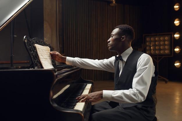 黒檀のピアニスト、スポット ライトでステージ上のジャズ パフォーマー。コンサートの前に楽器でポーズをとるミュージシャン