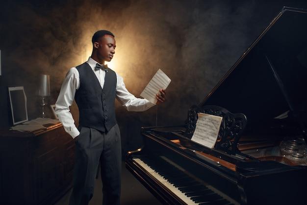 Пианист из черного дерева с нотной записью в руках на сцене с прожекторами. исполнитель позирует на музыкальном инструменте перед концертом