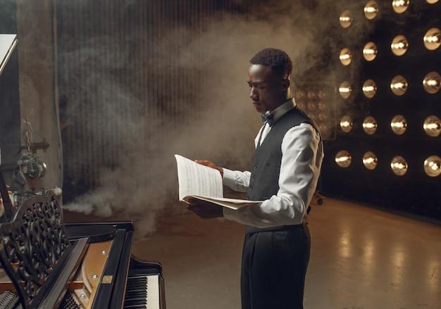 黒檀のピアニストが、音楽ノートを手にステージ ライトを当てたステージで。コンサートの前に楽器でポーズをとるパフォーマー