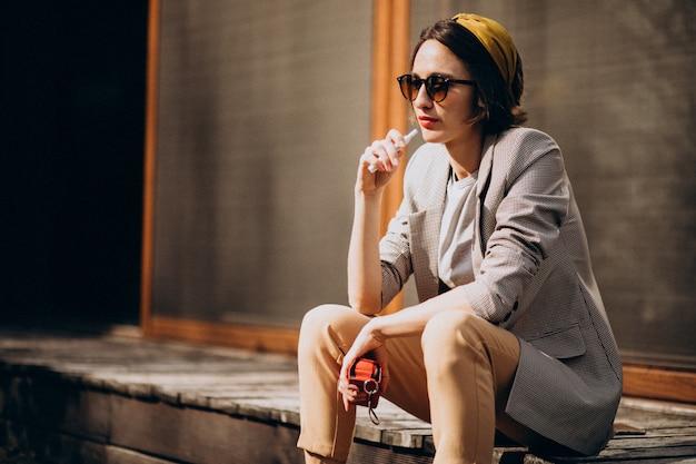 Молодая женщина сидит и курит ecigarette