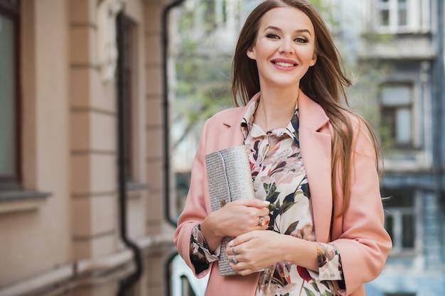 ピンクのコート春のファッショントレンドの財布を保持して街を歩いて魅力的なスタイリッシュな笑顔の女性を興奮