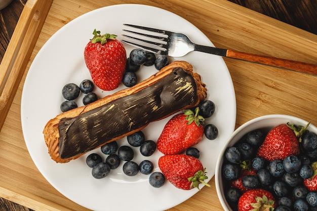 Торт эклер с шоколадной глазурью на деревянном подносе