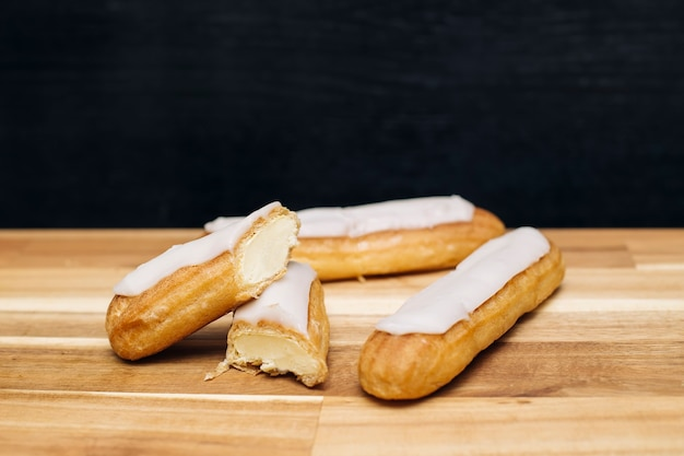 Eclair crispy creamy cake with white chocolate isolated on wooden surface