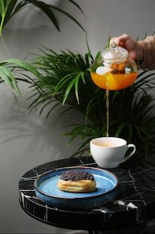 세라믹 접시에 eclair 대리석 돌과 배경에 열대 식물에 차 한잔. 찻주전자 붓기. 여자 손 잡고 주전자입니다. 차 튀김.