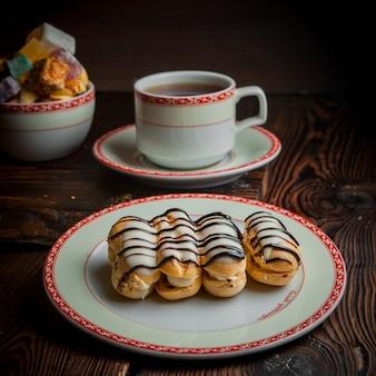Эклер с чашкой чая и сахаром в тарелке