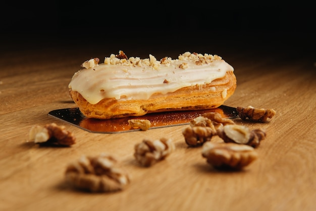 Eclair with glaze on wooden table