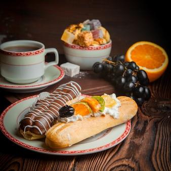 Эклер с виноградом и апельсином и чашка чая в тарелке