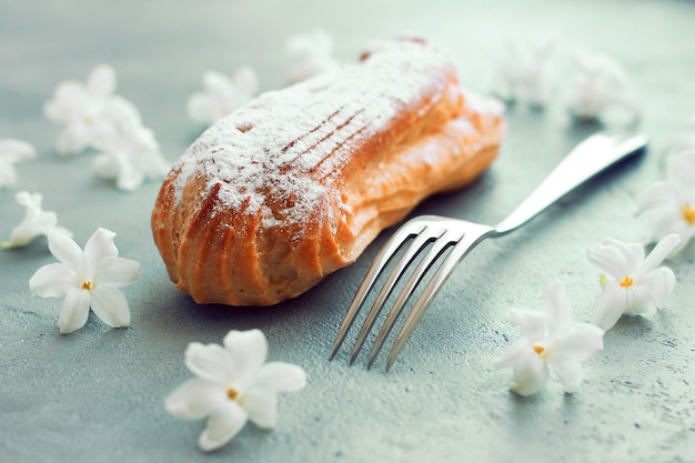Eclair with powdered sugar on a gray background, near a fork, flowers around the composition.