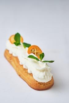 Эклер с белым сливочным кремом, украшенный мятой и кумкватом.