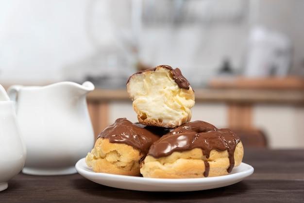 白いプレートにバタークリームを添えたチョコレートに浸したエクレア。