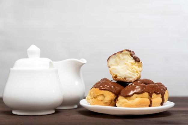 Эклеры, залитые шоколадом со сливочным кремом на белой тарелке