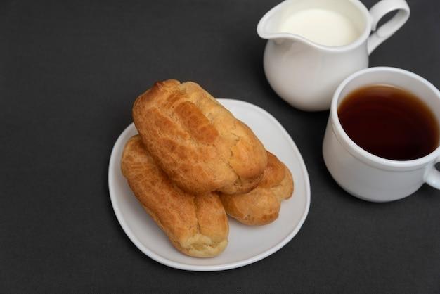 Эклеры к чаю с молоком. профитроли на белом блюдце. традиционные французские эклеры.
