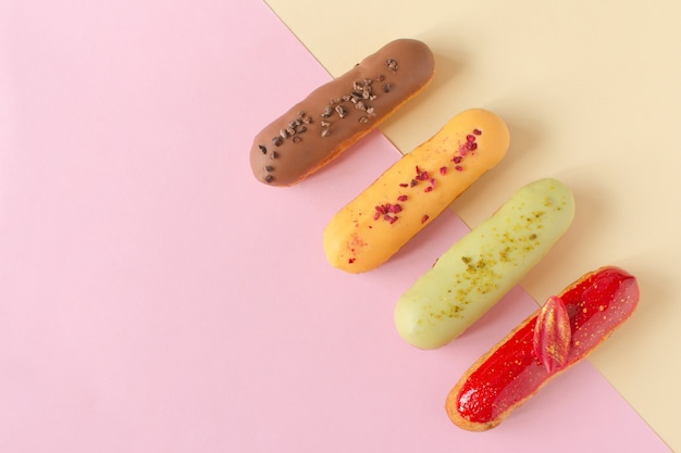 Эклеры на минимальном фоне. натюрморт привет десертное настроение. традиционный французский десерт с красочной глазурью. концептуальная выпечка, рецепты поваренной книги, баннер пекарни, реклама кафе.