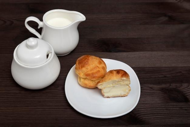 Эклеры на белой тарелке и чайный сервиз на деревянной поверхности. домашняя выпечка. выпечка к чаю.