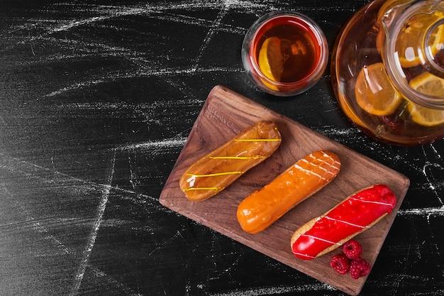 Эклеры на деревянной тарелке с напитком.