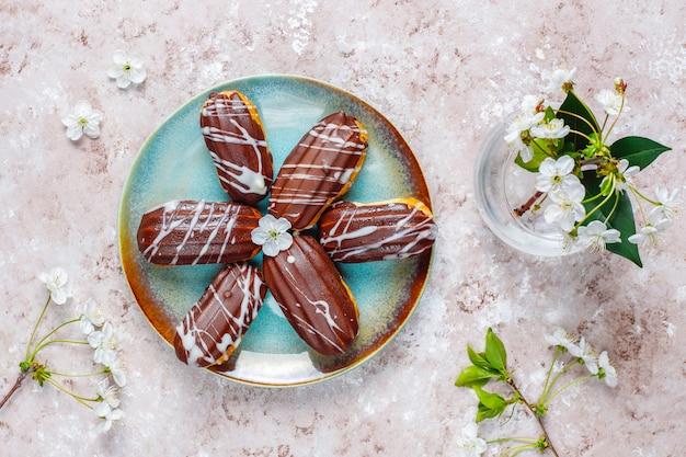 ブラックチョコレートとカスタード入りホワイトチョコレートのエクレアまたはプロフィットロール、伝統的なフランスのデザート。
