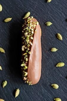 暗い背景にチョコレート釉薬、カルダモン、ピスタチオを添えたエクレアまたはプロフィットロール