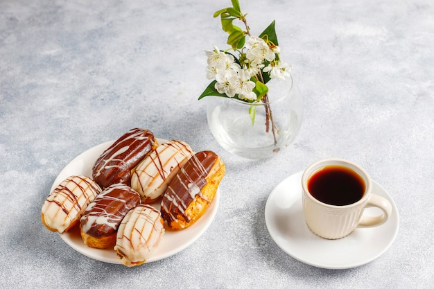 Eclairs or profiteroles with black chocolate and white chocolate with custard inside,traditional french dessert.