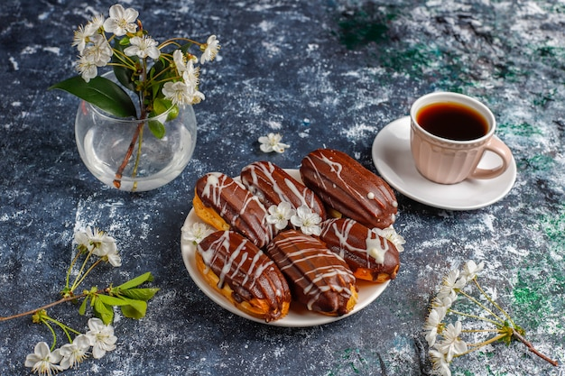 Eclairs or profiteroles with black chocolate and white chocolate with custard inside, traditional french dessert.