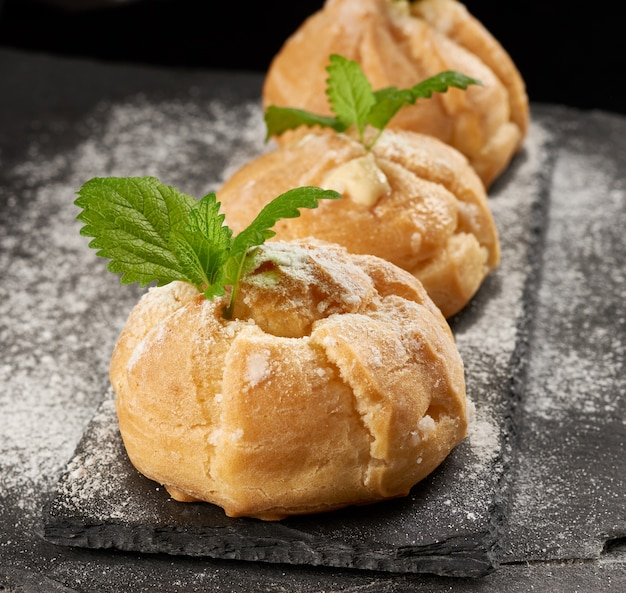 Eclairs and sprinkled with powdered sugar and decorated with a mint leaf