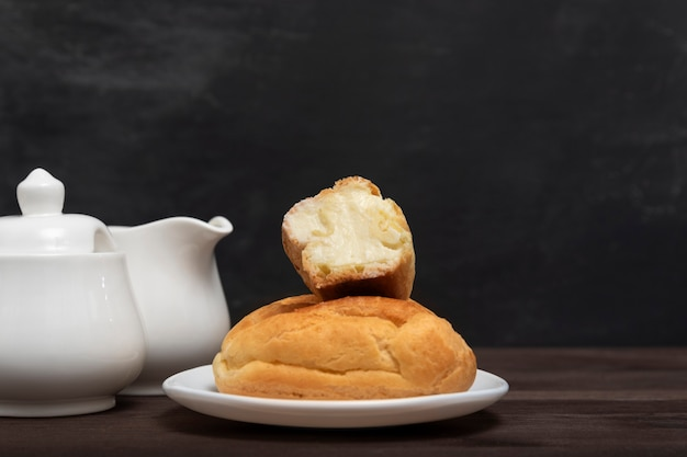 サービングプレートにバタークリームを添えたエクレア。お茶を焼く。伝統的なフランスのデザート。