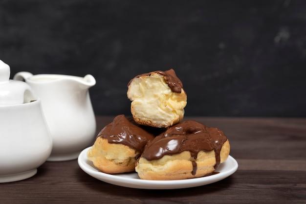 접시에 초콜릿 토핑과 버터 크림을 곁들인 에클 레어.