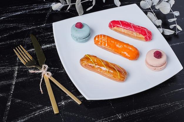 Eclairs con sciroppi colorati su un piatto bianco.