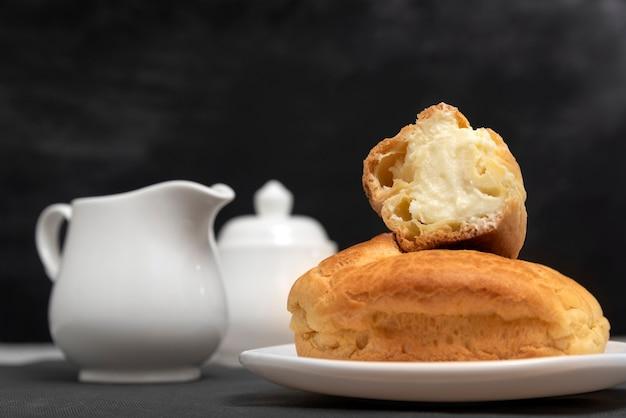 Эклеры с кремовой начинкой на тарелке рядом с кувшином. сладкая выпечка, крупный план. выпечка к чаю. домашние профитроли.